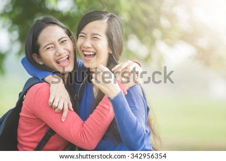 A portrait of happy two young Asian students laugh, joking around together - stock photo