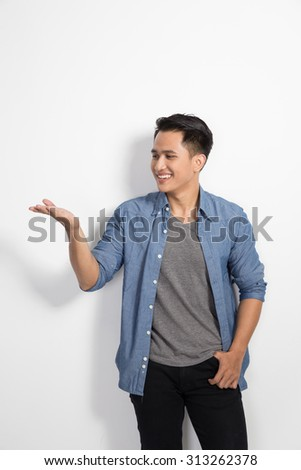 A portrait of happy young asian man smile to the camera, presenting hand gesture - stock photo