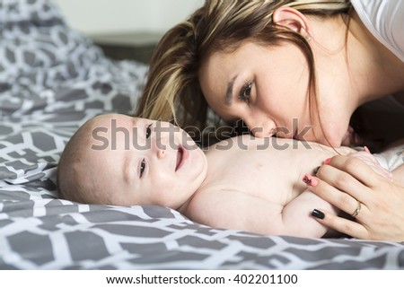 A Portrait of happy young mother with a baby in the bed at home - stock photo