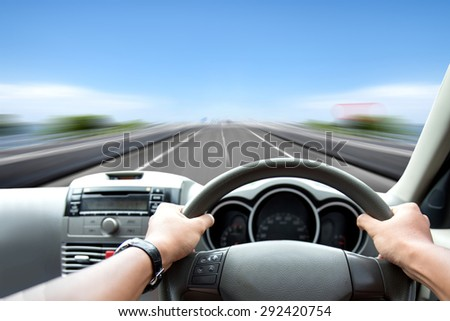 A portrait of Man's hand on steering wheel driving fast on the road - stock photo
