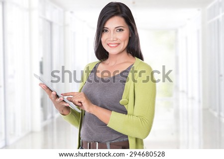 A portrait of middle aged asian woman holding a digital touch screen tablet - stock photo