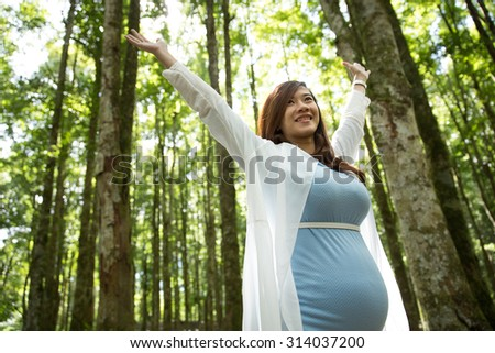 A portrait of Pregnant young woman enjoying the forest with open arms - stock photo