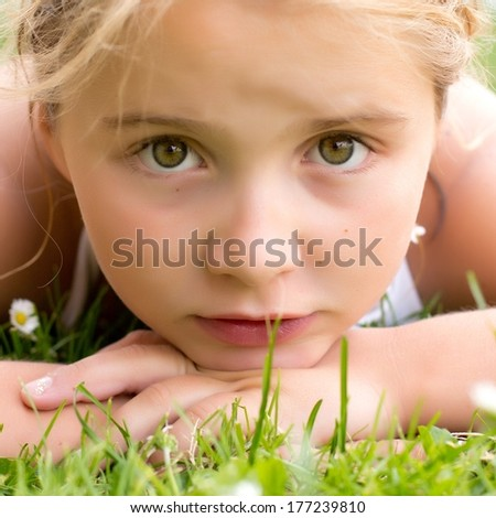 A portrait of sad child girl in grass - stock photo