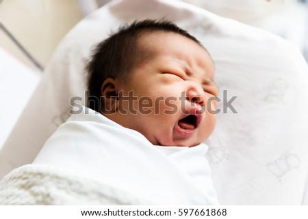 A portrait of sleepy cute newborn baby yawning 2 days after birth.