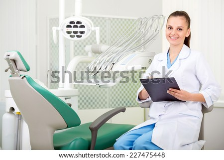 A portrait of the smiling woman dentist at her office. - stock photo