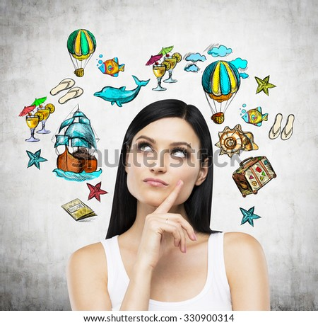 A portrait of thoughtful brunette who is surrounded by summer vacation icons which are drawn on the concrete wall. - stock photo