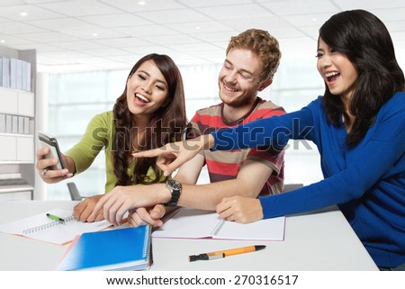 A portrait of three students laugh at something on a handphone