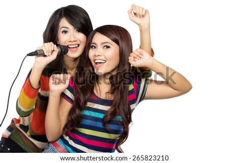 A portrait of two asian girls in striped t-shirt singing together - stock photo