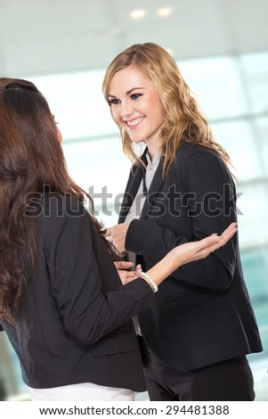 A portrait of two happy young businesswoman talking - stock photo