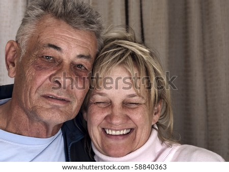 A portrait of two seniors expressing they're happiness and holding each other. - stock photo