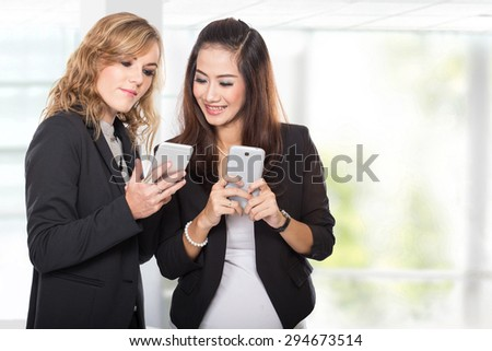 A portrait of two young businesswoman talking about something in the cellphone - stock photo