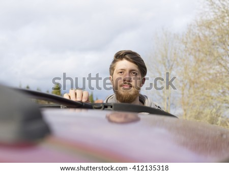 a portrait of young bearded scandinavian man standing closed to the car, outdoors non-urban, with wooden housing on the background - stock photo
