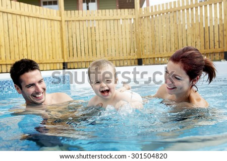 A Portrait of young family with baby and toddler in swimming pool - stock photo