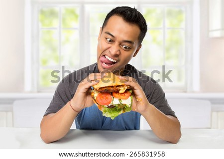 A portrait of young man have a great desire to eat a burger - stock photo