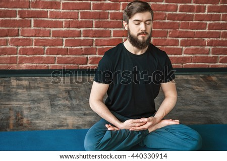 A portrait of young man with a beard and closed eyes wearing black T-shirt and blue trousers doing yoga position on blue matt at wall background, copy space, meditating - stock photo
