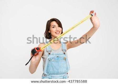 A portrait of young smiling beautiful girl, in gray shirt and denim overall, showing tape measure, looking at camera, isolated on white background - stock photo