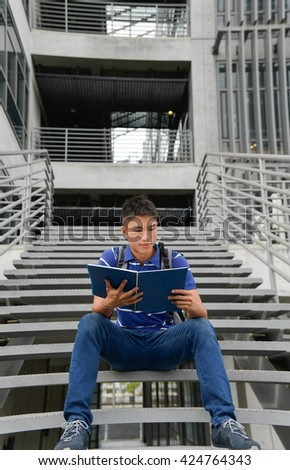 A portrait of young student holding book sitting at campus