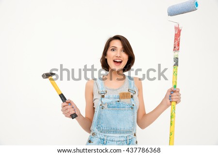A portrait of young surprised beautiful girl, in gray shirt and denim overall, holding hammer and painting roller, looking at camera, isolated on white background - stock photo
