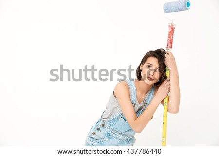 A portrait of young tired beautiful girl, in gray shirt and denim overall, holding painting roller, looking at camera, isolated on white background - stock photo