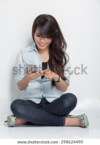 A portrait of young woman sitting on the floor while doing something with her smartphone - stock photo