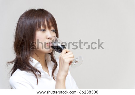 a portrait of young woman taking a red wine