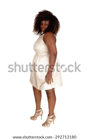 A portrait picture of a African American women in a beige dress and messy