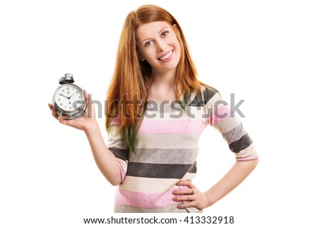 A portrait shot of a beautiful young girl smiling, holding an alarm clock, isolated on white background. - stock photo