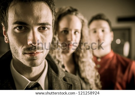 A portrait to two guys and a girl looking alike a movie poster - stock photo
