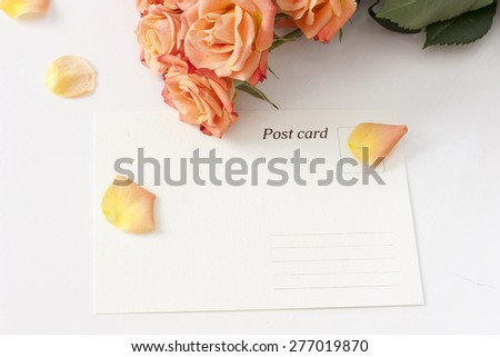 A post card with rose petals and tender tea roses in the background - stock photo