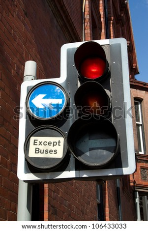 A post with traffic lights and a directional arrow and a sign with the words 'EXCEPT BUSES'.