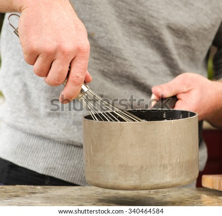 A pot being whisked - stock photo