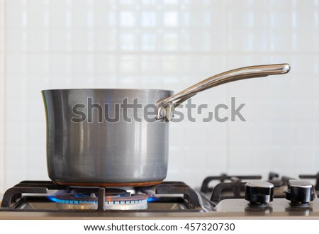 A pot on a gas cooker (boiling water for cooking) - stock photo