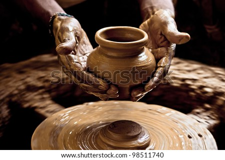 A potter first sculpts the pot, then in a single motion cuts it off the base using a thread, scoops the pot up and places it by the side. - stock photo