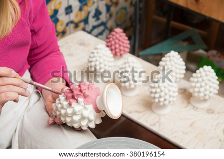 A pottery decorator painting a typical ceramic pine cone in his work table in Caltagirone, Sicily - stock photo