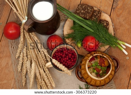 A pottery of cooked vegetables with meat, a crock of milk, a wooden board with a ripe tomato, cucumbers, rye bread and greens on it, and a metal cup of red currants on a wooden surface      - stock photo