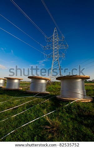 A power line tower in the field and bobbins with aluminum wire ready to installation - stock photo