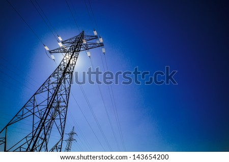 a power mast of a high voltage transmission line against blue sky with sun - stock photo