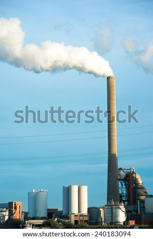a power plant along a river, steam transforms to electricity - stock photo