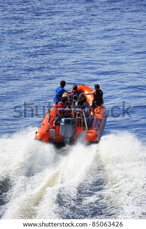 A powerboat heading out to sea at high speed leaving a white wake. Space for text on the water at top - stock photo