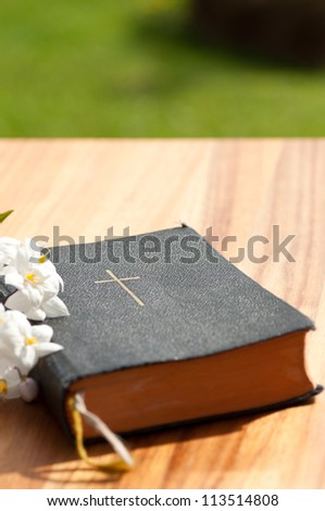A prayerbook with jasmine on a wooden table - stock photo
