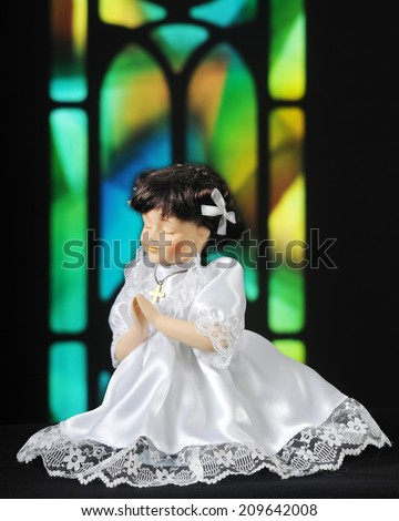 A praying doll dressed for communion, praying in front of a stained-glass window. - stock photo