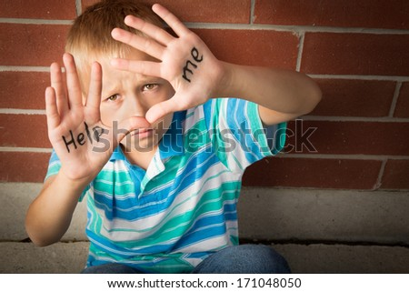 A pre-teen boy is begging to help him showing the message written on his palms - stock photo