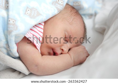 A precious 2 week old newborn baby girl is sleeping