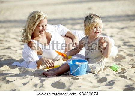 a pregnant mother plays sand with her daughter