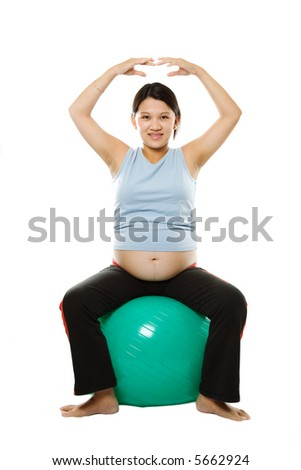 A pregnant woman exercising with an exercise ball