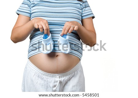 A pregnant woman holding a pair of baby shoes