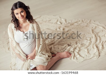 A pregnant woman in a beautiful home interior. - stock photo