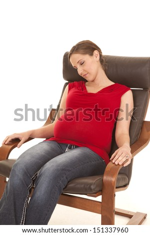 A pregnant woman in a chair sound asleep. - stock photo