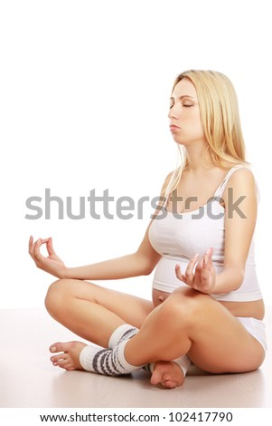 A pregnant woman meditating - stock photo