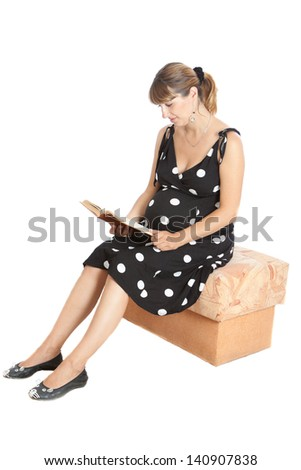A pregnant woman reads a book. Isolated on white - stock photo